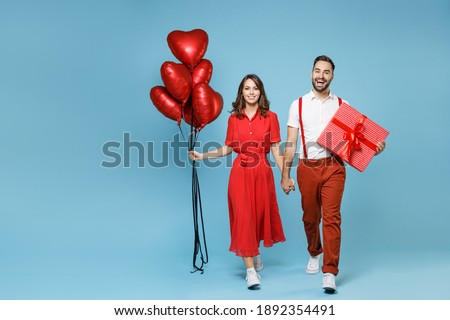 Full length cheerful young couple friends man woman in white red clothes celebrating birthday holiday party hold bunch air inflated helium balloons present box with gift isolated on blue background