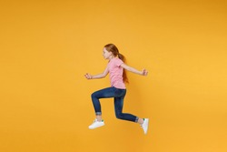 Full length children studio portrait side view of funny little ginger redhead kid girl 12-13 years old wearing pink casual t-shirt posing jumping like running isolated on yellow color wall background