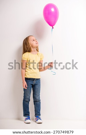 Full length. Cute little girl holding pink balloon on grey background.