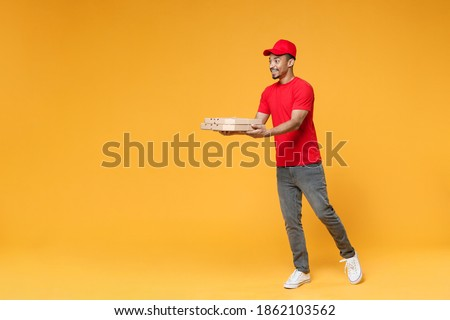 Full length delivery employee african man 20s in red cap blank print t-shirt uniform work courier dealer service concept hold give food order pizza cardboard boxes isolated on yellow background studio