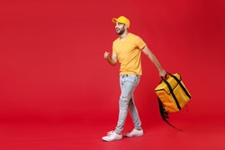Full length delivery employee man guy male 20s in yellow cap t-shirt uniform thermal food bag backpack work courier service during quarantine covid-19 virus standing isolated on red background studio