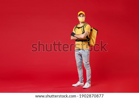 Full length delivery employee man in yellow cap face mask gloves t-shirt uniform thermal food bag backpack work courier service during quarantine coronavirus covid-19 virus isolated on red background