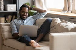 Full length dreamy young mixed race guy dating online in social network or chatting with girlfriend alone at home. Happy multiracial man relaxing on sofa, enjoying spending leisure time with laptop.