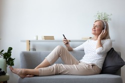 Full length elderly female music lover relaxing on couch wearing headphones holding smartphone enjoying song, daydreaming listens positive affirmations, favourite pastime, mood and harmony concept