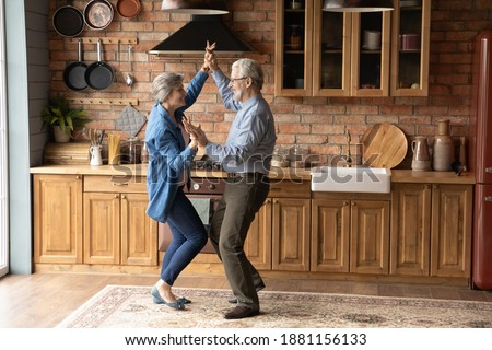 Full length energetic middle aged family couple dancing to disco music in kitchen. Happy old mature man and woman having fun, entertaining together indoors, involved in funny domestic activity.