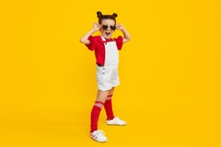 Full length excited hipster girl in stylish outfit trying on round shades while standing against yellow background