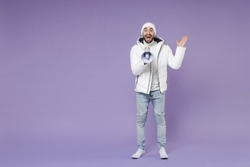 Full length excited man in warm white padded windbreaker jacket hat screaming in megaphone spreading hands isolated on purple background studio portrait. People lifestyle cold winter season concept