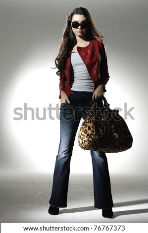 Full length Fashion girl in sunglasses with handbag posing in light background