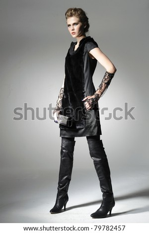 full-length fashion model in fashion dress posing in light background