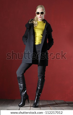 Full length fashion model in fashion dress with sunglasses posing wooden floor on red background
