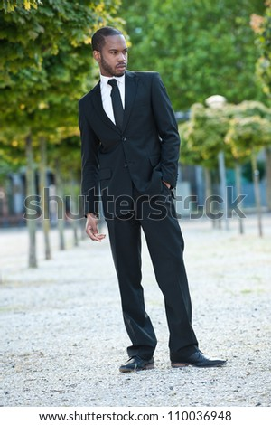 Full length fashion portrait of a handsome young African American businessman standing outdoors.