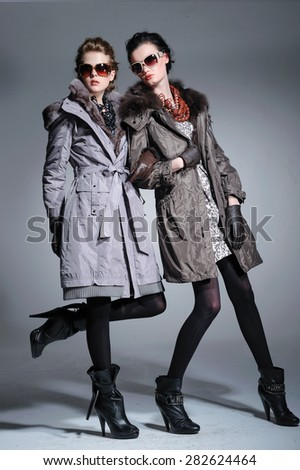 full-length fashion two model in coat clothes with sunglasses posing on light background