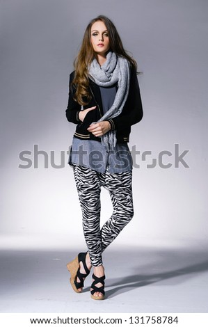 Full length fashion young girl in scarf posing on light background