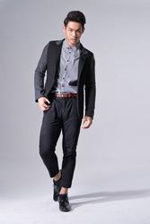 full length fashion young model wearing in suit with and pants , black shoes walking in studio