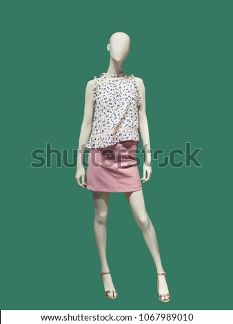 Full-length female mannequin dressed in casual clothes, isolated on green background. No brand names or copyright objects.