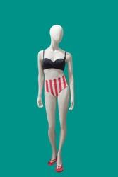 Full-length female mannequin wearing fashionable swimsuit, isolated on green background. No brand names or copyright objects.