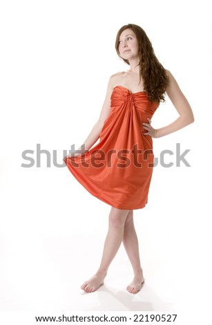 Full length front view of pretty teenage girl standing in orange dress.