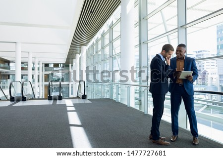 Full length front view of two young businessmen using tablet standing in the lobby of a modern business building. Modern corporate start up new business concept with entrepreneur working hard