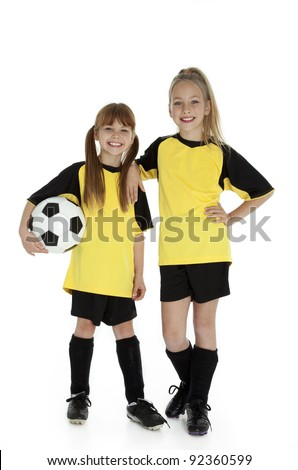 Full length front view of two young girls in soccer uniforms, holding soccer ball on white.