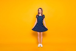 Full-length, fullbody portrait of nice, cheerful, positive, childish, comic, funny, cute girl, holding bottom of polka-dot dress with two hands, posing over yellow background