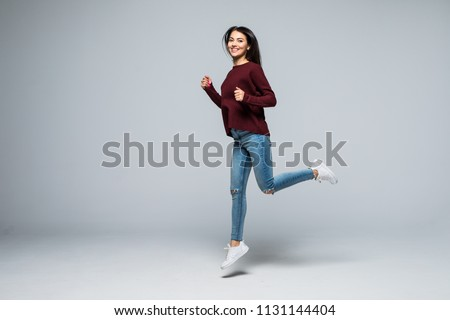 Full length, fullbody portrait of pretty, girlish coquette, charming, modern, stylish girl in denim outfit, pants, jumping in the air with raised leg, looking at camera, isolated on grey background