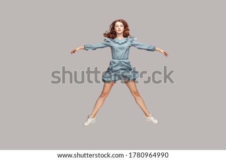 Full length girl vintage ruffle dress levitating hovering in mid-air, spread hands legs like a star, jumping trampoline, flying up and looking at camera. indoor studio shot isolated on gray background