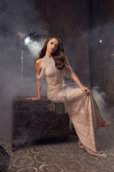 Full length gold hollywood stylish portrait. Elegant rich woman in expensive mermaid evening dress with wavy hair and makeup sitting at wooden box and posing in dark smoke interior with spot lights
