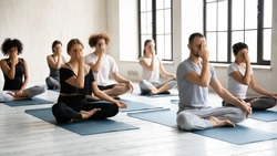 Full length group of young fit motivated focused multiracial people sitting in lotus position, practicing Alternate Nostril Breathing, finishing yoga session indoors with nadi shodhana pranayama.