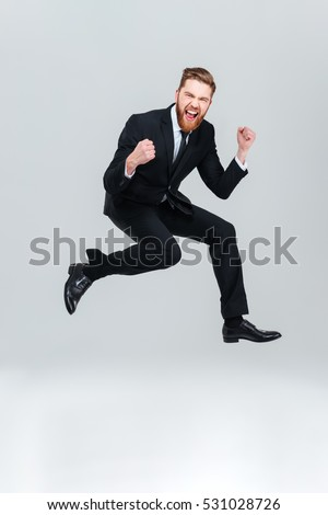 Full length happy business man in black suit jumping in studio and looking at camera with open mouth. Isolated gray background #531028726