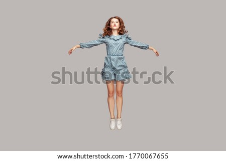 Photo of  Full length happy calm pretty girl in vintage ruffle dress levitating hovering in mid-air with raised hands as wings, jumping trampoline or flying up. indoor studio shot isolated on gray background