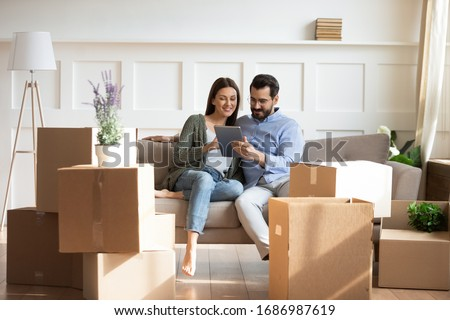 Full length happy family sitting on couch among cardboard boxes in new house, using digital tablet, buying decorations online. Smiling couple enjoying moving in new apartment, shopping in internet.