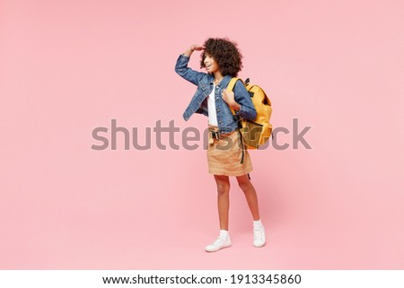 Full length happy little african american kid school girl 12-13 year old in casual clothes, backpack hand at forehead look far away distance isolated on pink background. Childhood education concept. Foto d'archivio ©