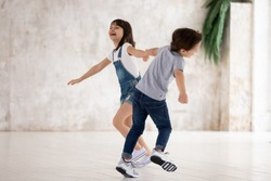 Full length happy little boy and girl holding hands, twisting, running, playing together, laughing. Energetic excited siblings having fun at home, engaged in indoors activity, feeling overjoyed.