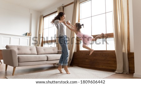 Full length happy mother holds hands spinning carefree adorable little daughter listen music moving in modern interior light cozy living room. Active funny games, lively play have fun together at home
