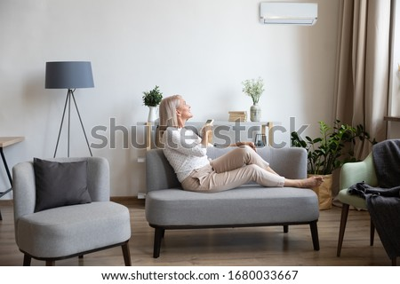 Full length happy older lady relaxing on cozy sofa in modern living room, turning on cooler system air conditioner with remote controller, enjoying fresh air, setting comfortable indoors temperature.