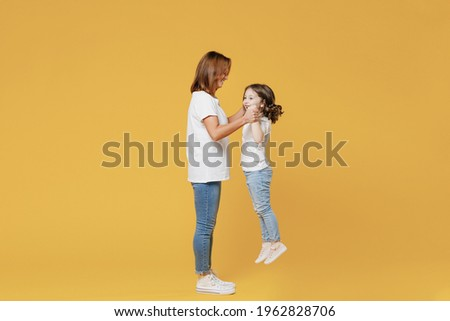 Full length happy woman in basic white t-shirt have fun hold on hands cute child baby girl 5-6 years old Mom mum little kid daughter isolated on yellow color background studio Mother's Day love family Stock photo ©
