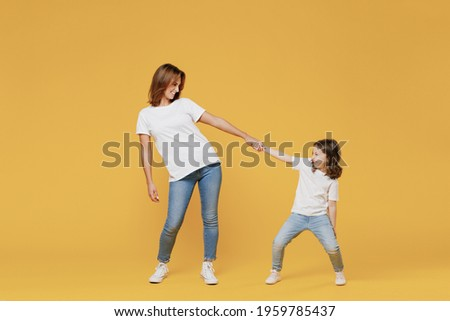 Full length happy woman in basic white t-shirt have fun with cute child baby girl 5-6 years old hold hands. Mom little kid daughter isolated on yellow color background studio. Mother's Day love family