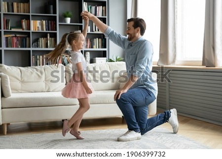 Full length happy young daddy standing on one knee, twisting smiling adorable preschool kid daughter in princess dress, practicing waltz or preparing performance, dancing together in living room.