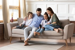 Full length happy young family couple relaxing on comfortable sofa with smiling two little children siblings, using smartphone. Joyful parents spending free weekend time with kids in living room.