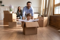 Full length happy young father in glasses pushing carton box with small kid son in new living room. Overjoyed family couple having fun with little child, celebrating moving into flat apartment.