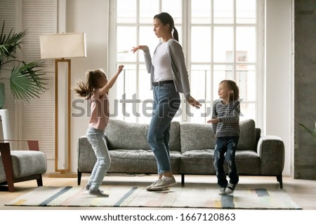 Full length happy young mother dancing with small children siblings in living room. Small energetic kids brother sister having fun with positive nanny together at home, enjoying daycare time.