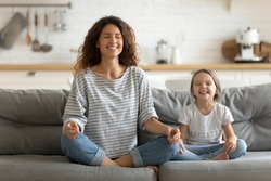 Full length happy young nanny mom sitting on sofa in lotus pose, teaching small daughter yoga breathing exercise. Friendly sincere two female generations family relaxing on couch, healthcare concept.