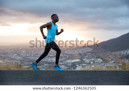 Full length horizontal shot of fast male runner enjoys speed, photographed in motion, runs along road with mountain and city view in background. Running at dawn concept. Strong sportsman outside #1246362505