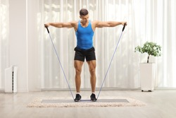 Full length hot of a muscular guy exercising with a resistance band at home