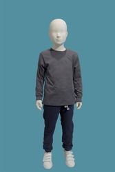 Full length image of a child display mannequin dressed in brown sweater and blue jeans isolated on a blue background.