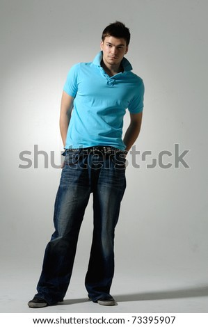 Full length image of a handsome young guy standing on gray background