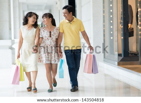Full-length image of a happy family walking in the shopping-mall together