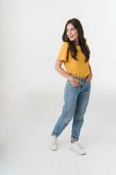 Full length image of attractive brunette woman wearing casual clothes smiling and looking at copyspace isolated over white background