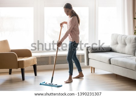 Full-length image of barefoot young woman stands in living room homeowner doing house chores cleaning wooden laminate floor using microfiber wet mop pad, housekeeping job or routine home work concept