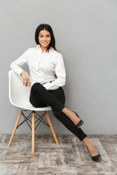 Full length image of beautiful businesslike woman in formal wear sitting on chair in office isolated over gray background
